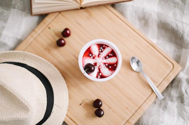 Composition estivale avec livre de glace à la cerise et vue de dessus de chapeau de paille