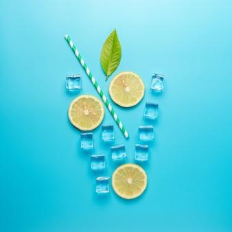 Composition d'été créative avec des tranches de citron, de paille et de glaçons sur une surface bleue.