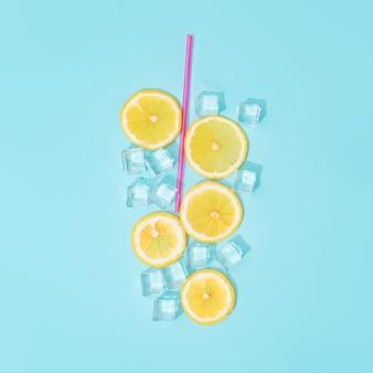 Composition d'été créative avec des tranches de citron, de la paille et des glaçons.