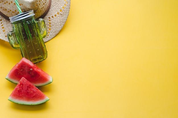 Composition d'été avec pastèque, chapeau et récipient pour jus sur fond jaune. concept d'été. copiez l'espace. mise à plat.