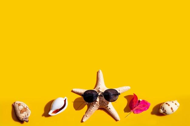 Composition d'étoiles de mer avec lunettes de soleil et fleur avec coquillages exotiques sur fond jaune.