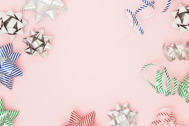 Composition festive avec des arcs de traction d'emballage sur une surface rose