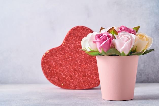 Composition festive avec de belles fleurs roses délicates dans une boîte ronde rose avec un coeur rouge sur fond gris clair. mise à plat, copiez l'espace.