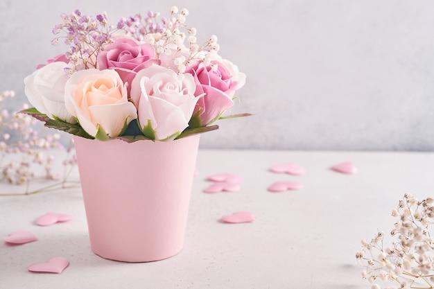 Composition festive avec de belles fleurs roses délicates dans une boîte ronde rose sur fond gris clair. mise à plat, copiez l'espace.