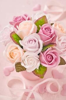 Composition festive avec de belles fleurs roses délicates dans une boîte ronde rose sur fond rose clair. mise à plat, copiez l'espace. carte de voeux.