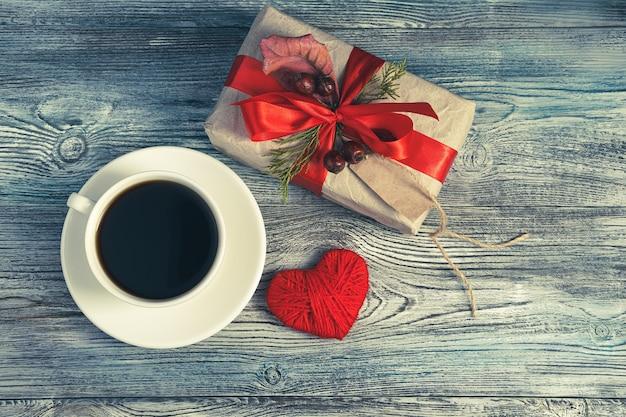 Composition festive avec un cadeau, un café et un cœur sur un fond en bois gris-bleu.