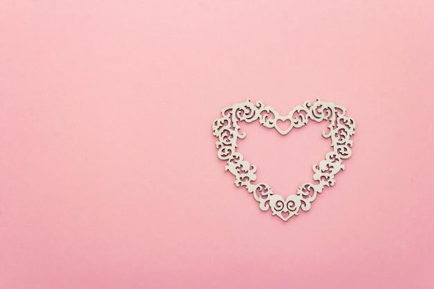Composition festive avec coeur blanc ajouré sur fond rose. concept de la saint-valentin ou de mariage. vue de dessus, espace copie, mise à plat
