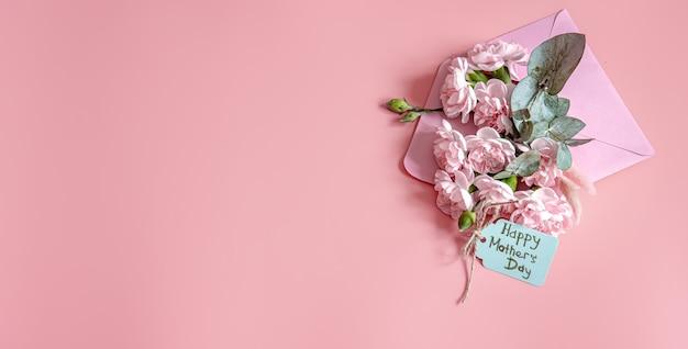 Composition festive avec une enveloppe avec des fleurs fraîches et l'inscription à plat happy mother's day.