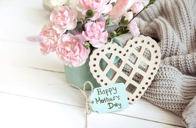 Une composition festive avec des fleurs fraîches dans un vase, des éléments décoratifs et un souhait pour une bonne fête des mères sur une carte postale.