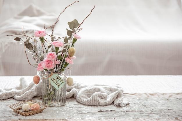 Composition festive joyeuses pâques avec des fleurs dans un vase en verre et des détails de décoration sur l'espace de copie de table.