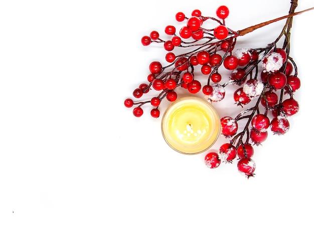 Composition festive de noël ou du nouvel an avec des baies de houx rouges dans la neige et une bougie de cire brûlante sur fond blanc