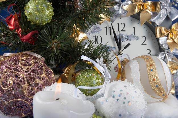 Composition festive de noël avec horloge, diverses bougies de boules de vacances et autres ornements