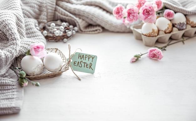 Composition festive de pâques avec des oeufs, des fleurs et l'inscription happy easter copy space.
