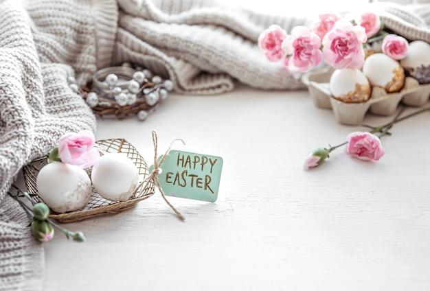 Composition festive de pâques avec des oeufs, des fleurs et l'inscription happy easter copy space