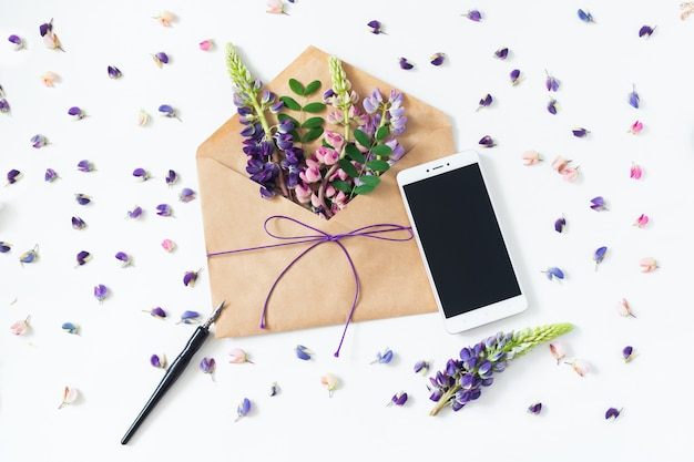 Composition festive: sur une table blanche se trouvent une enveloppe, un cahier, un stylo-plume et des fleurs.