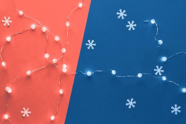 Composition festive de vacances d'hiver en corail et bleu. nouvel an ou motif de noël à plat poser vue de dessus noël flocons de neige en papier décoratif et guirlande de lumières festives, papier deux tons.