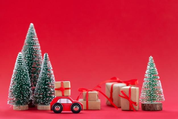 Composition festive voiture rouge de noël avec une boîte-cadeau dans une forêt de pins où de nombreux cadeaux différents sur fond rouge. concept de carte de bonne année.