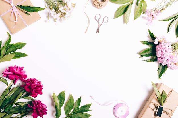 Composition de fête sur fond blanc: fleurs de pivoines et d'oeillets, cadeaux, rubans, papier d'emballage