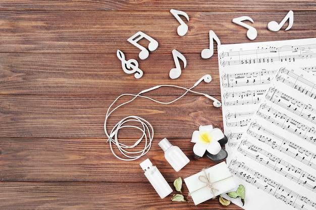 Composition de feuilles de musique et de fournitures de spa sur fond de bois