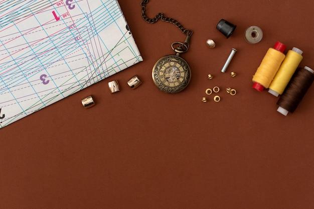 Composition avec fils à coudre et accessoires sur fond blanc, vue de dessus