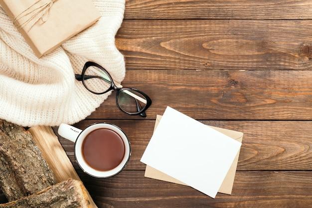 Composition de flatlay avec écharpe tricotée blanche, tasse de thé, bois de chauffage, lettre, carte de papier vierge, verres sur la table de bureau en bois