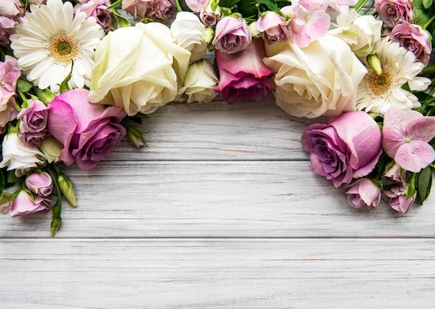 Composition de fleurs. bordure faite de fleurs roses sur fond en bois blanc. mise à plat, vue de dessus, espace copie