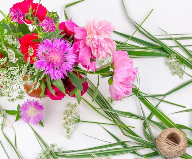 Composition de fleurs avec un bouquet de pivoines roses, de bleuets et de roses rouges sur fond blanc, vue de dessus à plat