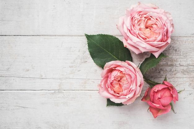 Composition de fleurs de boutons de rose roses et feuilles sur une surface en bois blanche.