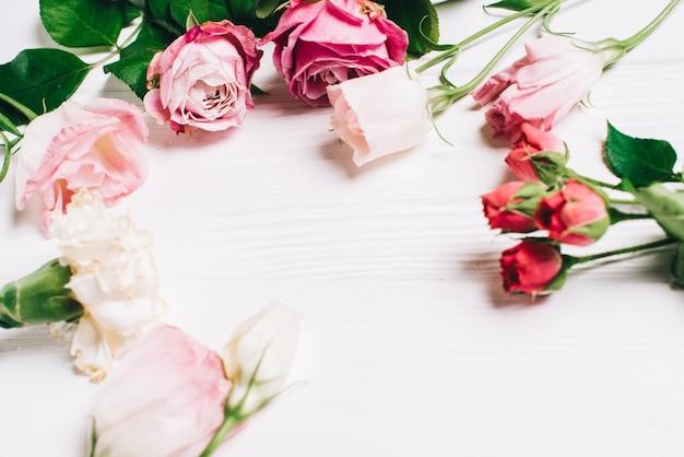 Composition des fleurs. cadre en fleurs et feuilles roses. vue de dessus, plat