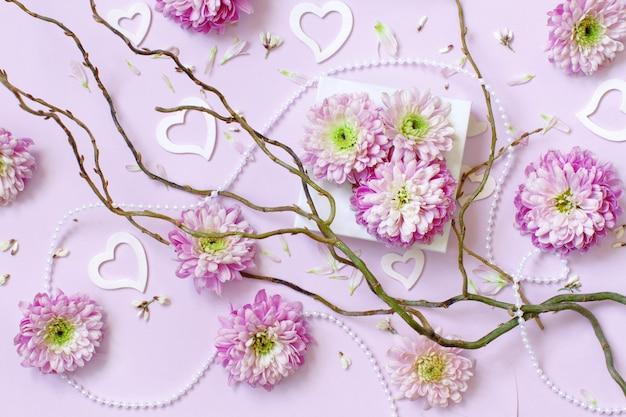 Composition de fleurs avec des coeurs sur fond rose pastel
