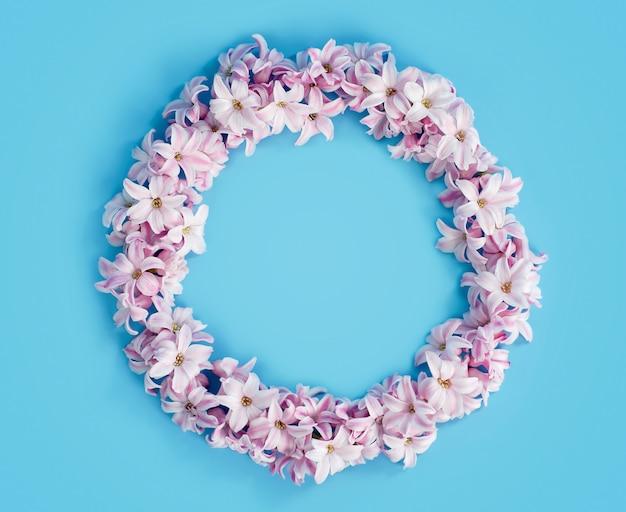 Composition de fleurs. couronne faite de fleurs rose jacinthe sur fond bleu en forme de cadre.