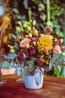 Composition de fleurs dans le seau roses chrysanthème vue latérale
