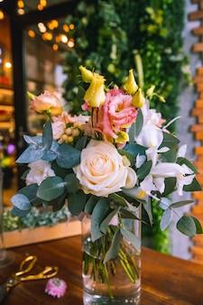 Composition de fleurs dans un vase en verre roses roses blanches et orange lithianthus vue latérale