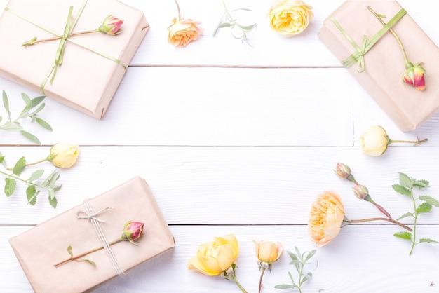 Composition de fleurs festives. espace de travail avec des fleurs roses jaunes, cadeau. vue de dessus, mise à plat. concept d'anniversaire, de mère, de saint-valentin, de femme, de jour de mariage