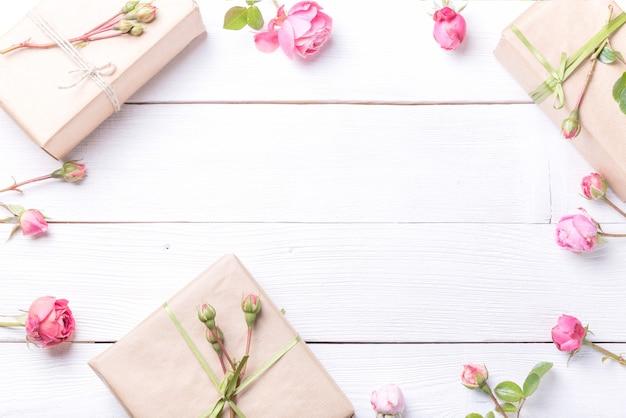 Composition de fleurs festives. espace de travail avec des fleurs roses roses, cadeau. vue de dessus, mise à plat. concept d'anniversaire, de mère, de saint-valentin, de femme, de jour de mariage