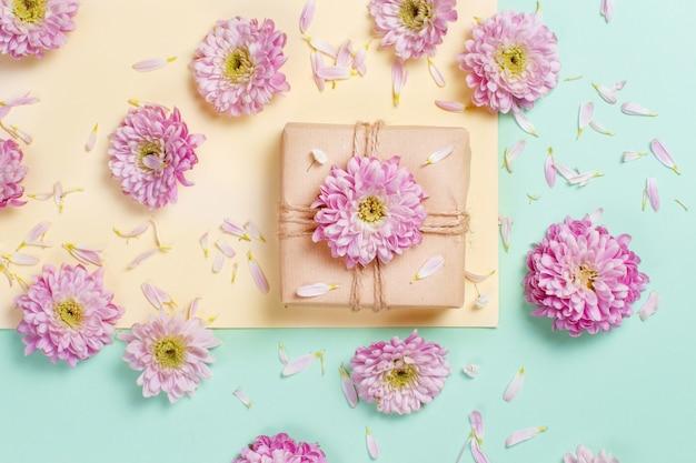 Composition de fleurs avec des fleurs, des pétales et une boîte cadeau sur fond pastel