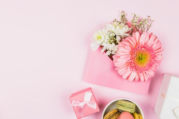 Composition de fleurs fraîches dans l'enveloppe près du présent et des macarons