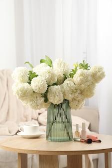 Composition avec des fleurs d'hortensia, une tasse de café et des cosmétiques. plante de printemps