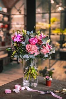 Composition de fleurs mélange roses chrysanthèmes ruban ciseaux vue latérale