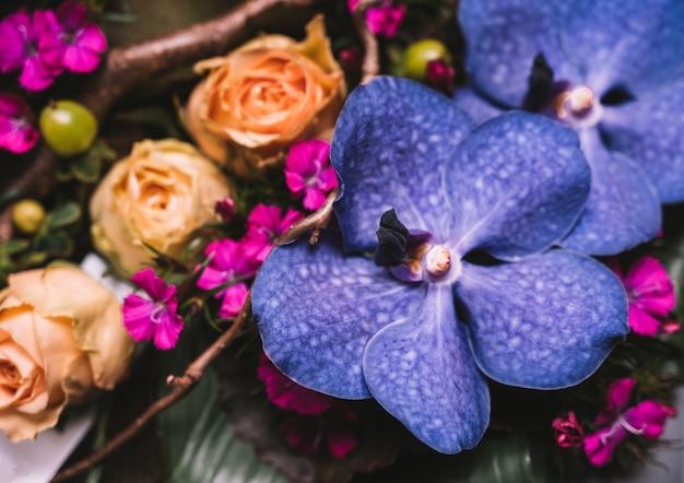 Composition de fleurs avec des orchidées violettes et des roses roses tendres