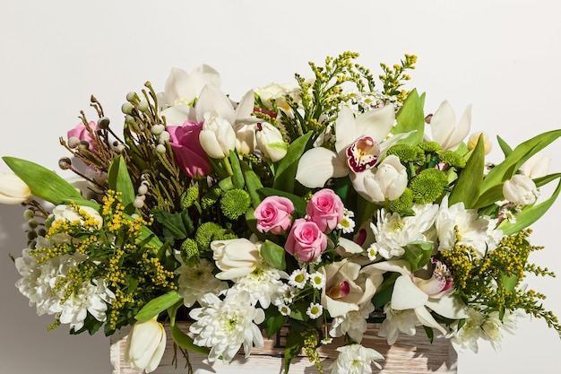 Composition de fleurs de roses roses orchidées blanches tulipes rouges jacinthe et hrzemtem