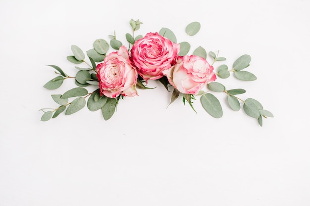 Composition florale avec boutons de fleurs roses roses et eucalyptus sur fond blanc. mise à plat, vue de dessus