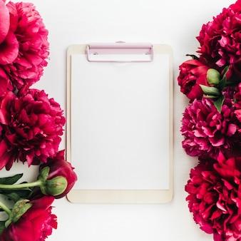 Composition florale avec cadre de fleurs de pivoine rouge et presse-papiers sur une surface blanche