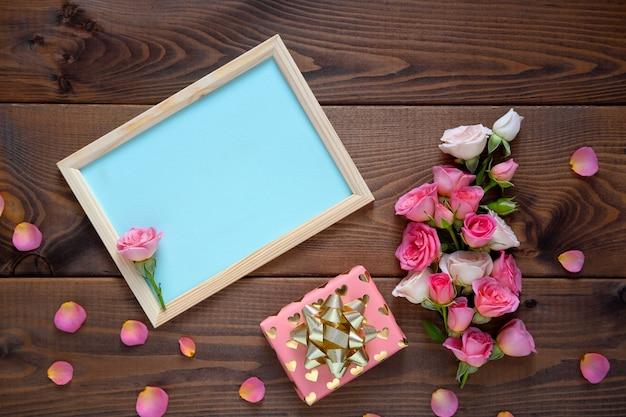 Composition florale avec une couronne de roses roses sur fond en bois. contexte de la saint-valentin. mise à plat, vue de dessus.