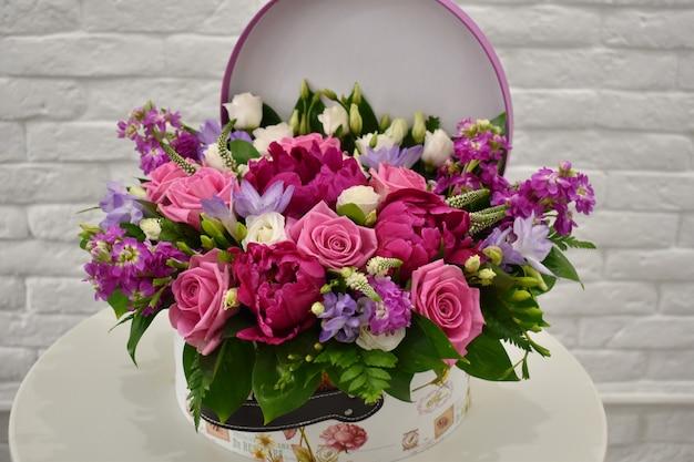 Composition florale dans le tronc d'origine. belles fleurs dans une élégante boîte à chapeau