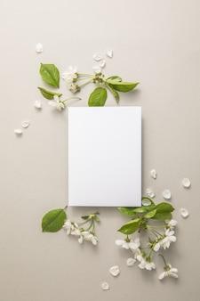 Composition florale élégante avec du papier vierge au centre du fond gris