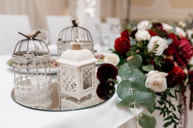 Composition florale avec eucalyptus, roses blanches et bordeaux sur la table et cages en métal sur un plateau miroir