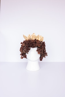 Composition florale avec fleurs brunes séchées avec pot en forme de tête