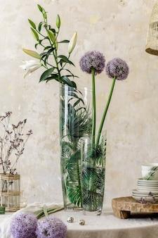 Composition florale à l'intérieur de la cuisine avec table familiale en bois, belles fleurs en vase, assiettes, tasses, plateau et décoration élégante. salle à manger dans un décor moderne. modèle.
