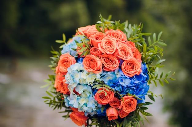 Composition florale orange et bleue pour un mariage : roses oranges et pied d'alouette bleu.